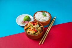Asian fried tofu,sliced vegetable, mushroom shiitake, cut lime and chopstick on red- blue background. Stock Photos