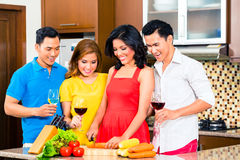 Asian friends cooking  for dinner party. Asian friends cutting vegetables cooking together in domestic kitchen for dinner party, drinking wine Stock Photography