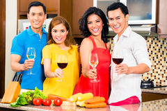 Asian friends cooking  for dinner party. Asian friends cutting vegetables cooking together in domestic kitchen for dinner party, drinking wine Stock Image