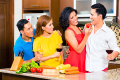 Asian friends cooking  for dinner party. Asian friends cutting vegetables cooking together in domestic kitchen for dinner party, drinking wine Royalty Free Stock Image