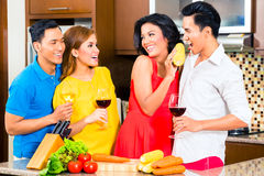 Asian friends cooking  for dinner party. Asian friends cutting vegetables cooking together in domestic kitchen for dinner party, drinking wine Royalty Free Stock Images