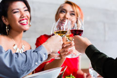 Asian friends dining in fancy restaurant Stock Photography