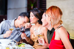 Asian friends dining in fancy restaurant Stock Images