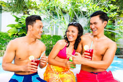 Asian friends drinking cocktails at pool Stock Photo