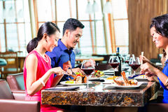 Asian Friends eating  in restaurant Royalty Free Stock Photography