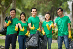Asian friends with full bin bags Stock Photo