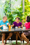 Asian friends having coffee on home porch Stock Photos