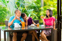 Asian friends having coffee on home porch Royalty Free Stock Images