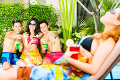 Asian friends partying at pool party in hotel Royalty Free Stock Images