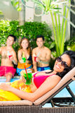 Asian friends partying at pool party in resort. Asian friends partying and drinking fancy cocktails at hotel or club pool party stock photo