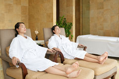 Asian Friends Relaxing in Spa Salon. Attractive Vietnamese friends wearing bathrobes relaxing on lounge chairs while enjoying weekend in spa salon stock image