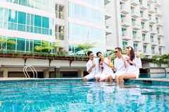 Asian Friends sitting by hotel swimming pool Royalty Free Stock Images