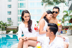Asian Friends sitting by hotel swimming pool Stock Photography