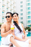 Asian Friends sitting by hotel swimming pool Stock Image