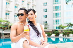Asian Friends sitting by hotel swimming pool Stock Photos