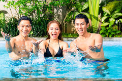 Asian friends swimming in pool Royalty Free Stock Images