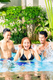 Asian friends swimming in pool Royalty Free Stock Photo