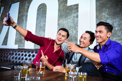 Asian friends taking pictures or selfies in fancy night club. Asian party people group of young friends taking pictures or selfies with their mobile or cell Royalty Free Stock Image