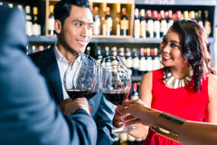 Asian friends toasting with red wine in bar Stock Image