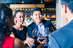 Asian friends toasting with red wine in bar Stock Images