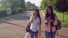 Asian friends walking on the street using gadgets. Two happy smiling girls going on pavement use smartphone. Vietnamese girl talking on mobile phone and stock video