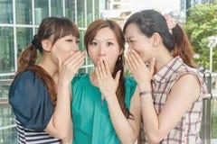 Asian friends' whisper. Closeup portrait Stock Photos