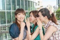 Asian friends' whisper. Closeup portrait Stock Photography