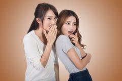 Asian friends' whisper. Full length portrait Stock Photo