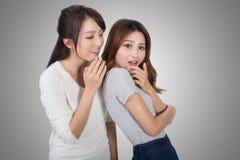 Asian friends' whisper. Full length portrait Royalty Free Stock Photos