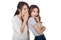 Asian friends' whisper. Full length portrait Royalty Free Stock Image