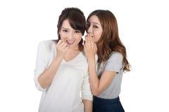 Asian friends' whisper. Full length portrait Stock Photos