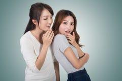 Asian friends' whisper. Full length portrait Royalty Free Stock Photo