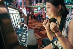 Asian gambling in casino playing slot machines. Asian woman gambling in casino playing on slot machines spending money. Gambler addict to spin machine. girl royalty free stock images