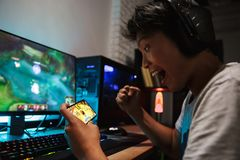 Asian gamer boy screaming while playing video games on smartphon. E and computer in dark room wearing headphones and using backlit colorful keyboard stock photo