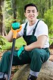 Asian gardener keeping a spade Royalty Free Stock Photos