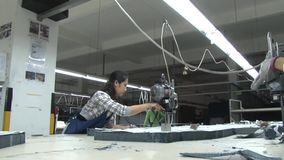 Asian Garment Industry Factory: Workers at a fabric cutting table with bandsaw stock footage