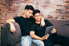 Asian gay couple watching and looking at phone tablet together. Portrait of happy gay men - Homosexual love concept. Asian gay couple watching and looking at stock images