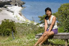 Asian girl. Sitting on a wooden bench with ocean in the background Royalty Free Stock Photo