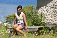 Asian girl. Sitting on a wooden bench with ocean in the background Royalty Free Stock Image
