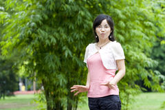 Asian girl. Poses with fingers out happily in a park at the background of bamboo forest Stock Images