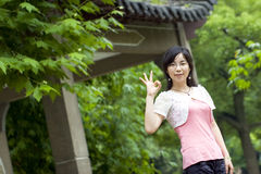 Asian girl. Poses 'OK'  in a park at the background of bamboo forest and a summerhouse Stock Image