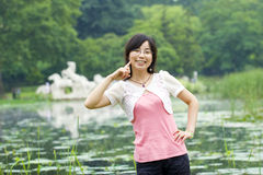 Asian girl. Smiles with a finger pointing at her face in a park at the background of a lake and some horse sculpture far away Stock Photography