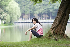 Asian girl. Sits aside an old tree in a park Royalty Free Stock Photography