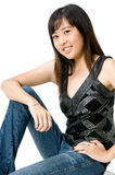 Asian Girl. A cute young Asian woman in black and silver top and jeans on white background Royalty Free Stock Image