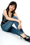 Asian Girl. A cute young Asian woman in black and silver top and jeans on white background Stock Photo