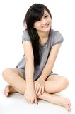Asian Girl. A cute Asian teenager sitting on white background Royalty Free Stock Image
