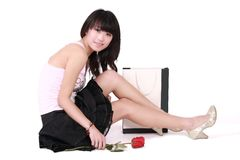 Asian girl. A beautiful Asian girl with rose and shopping sits on white Royalty Free Stock Photos