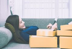 Asian Girl addicted to online shopping, full of delivered boxes royalty free stock images