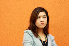 An asian girl with angry face. She shows a very angry expression, probably she just faced something unexpected Stock Photo