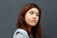 An asian girl with angry face. She shows a very angry expression, probably she just faced something unexpected Royalty Free Stock Image